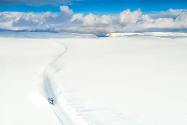 Snow plow on empty snowy road to Nordkapp, Finnmark, Norway