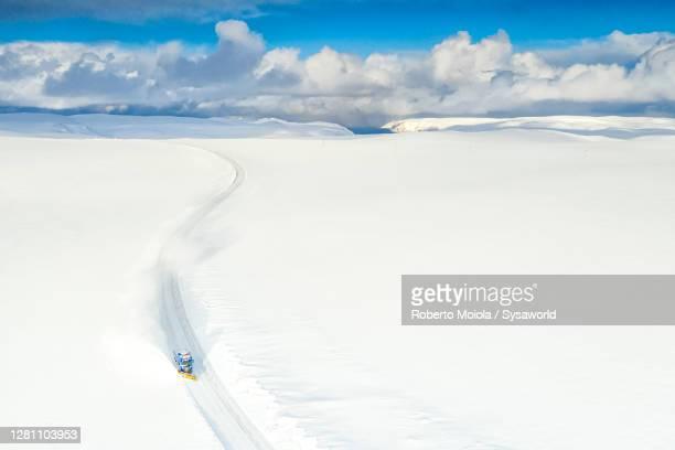 snow plow on empty snowy road to nordkapp, finnmark, norway - extreem weer stockfoto's en -beelden