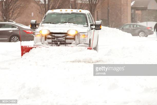 snow plow removing snow at an apartment complex - snowplow stock pictures, royalty-free photos & images