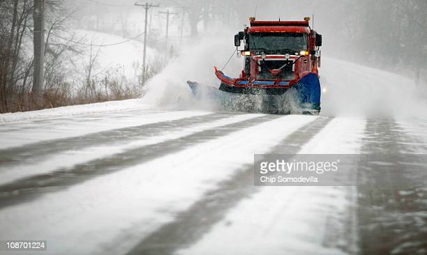 A snow plow truck clears suburban roads as the wind picks up and snow begins to fall February 1 2011 in Iowa City United States The National Weather...