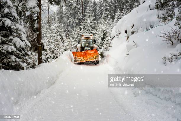 schneepflug in winterlandschaft in österreich arbeiten - schneefahrzeug stock-fotos und bilder