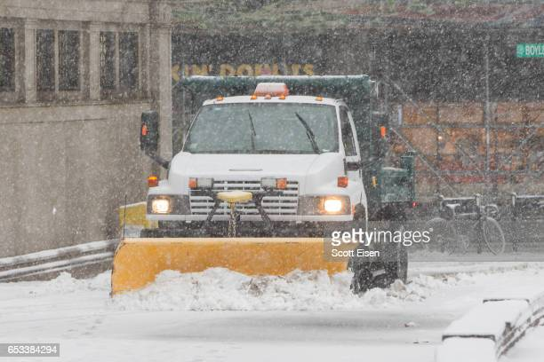 A snow plow works to clear snow near Boylston St as Winter Storm Stella bears down on March 14 2017 in Boston Massachusetts
