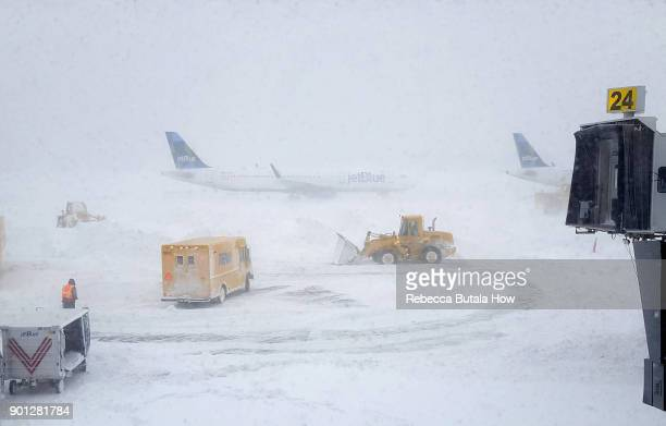 Snow plows move snow as a JetBlue airplane waits outside terminal five at John F Kennedy International Airport on January 4 2018 in the Queens...