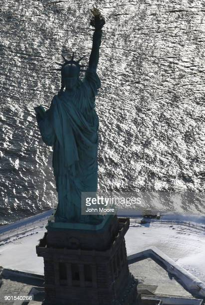 A snow plows next to the Statue of Liberty on January 5 2018 in New York City New York City dug out from the 'Bomb Cyclone' under frigid temperatures