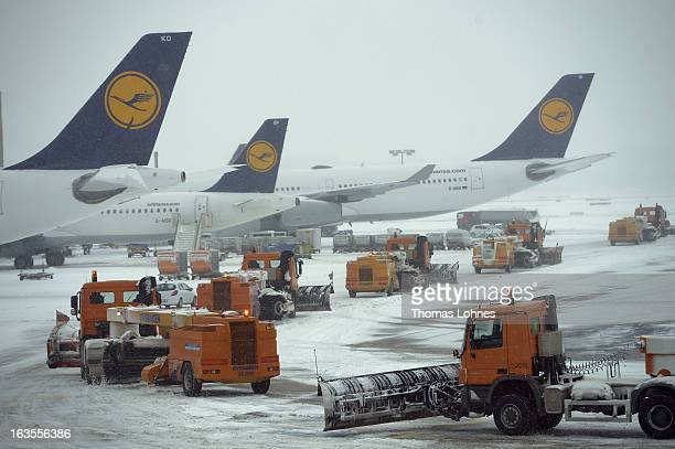 Snow plows pass Lufthansa airplanes on there way to the runway at Frankfurt International Airport on March 12 2013 in Frankfurt am Main Germany They...