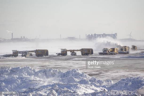 Snow removal equipment operators work the taxiway and runways at Logan International Airport following a 'bomb cyclone' the previous day on January 5...