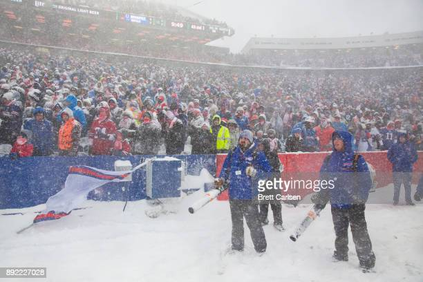 Snow removal workers and fans watch game action between the Buffalo Bills and the Indianapolis Colts during the first quarter at New Era Field on...