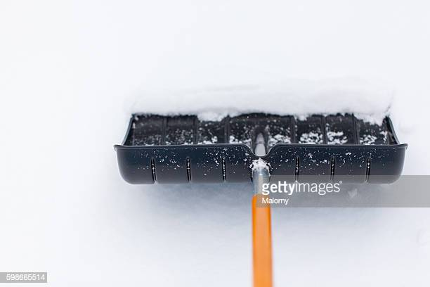 snow shovel in snow, during snowfall. shoveling the snow - snow shovel stock photos and pictures