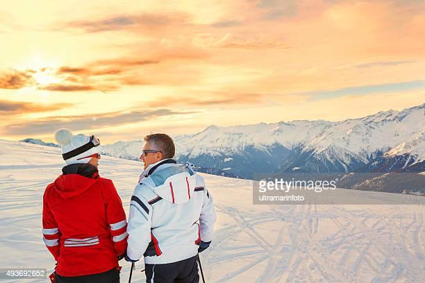 Neige, skieurs couple profitant de magnifiques montagnes paysage d'hiver au coucher du soleil