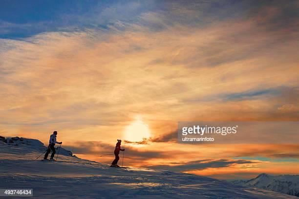 スノースキーのカップル楽しみながら、美しい山の夕日の冬景色 - マドンナディカンピリオ ストックフォトと画像
