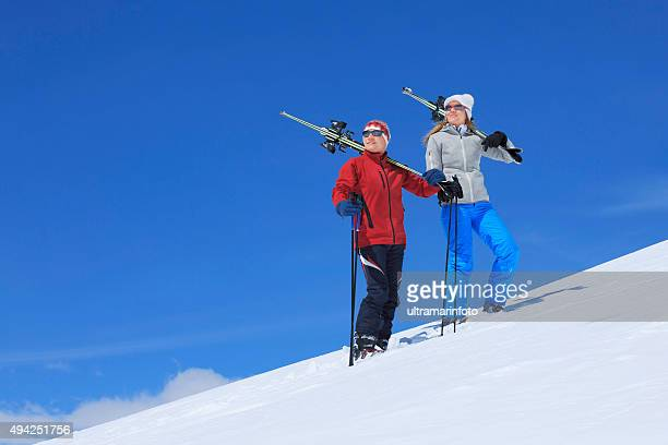 Snow skiers couple  Happy mature women and men carrying skis