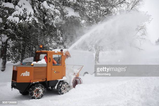 Snow sprays from a snow blower as a worker clears a road during preparations ahead of the World Economic Forum in Davos Switzerland on Monday Jan 22...