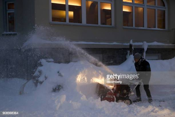 Snow sprays from a snow blower as a worker clears a street outside a hotel in Davos Switzerland on Sunday Jan 21 2018 World leaders influential...