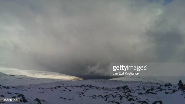 snow squall over the fjord - snow squall stock photos and pictures