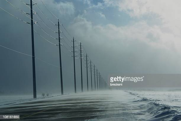 snow squalls covering rural highway road - snow squall stock photos and pictures