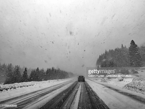 snow storm and car on a road in quebec - blizzard stock pictures, royalty-free photos & images