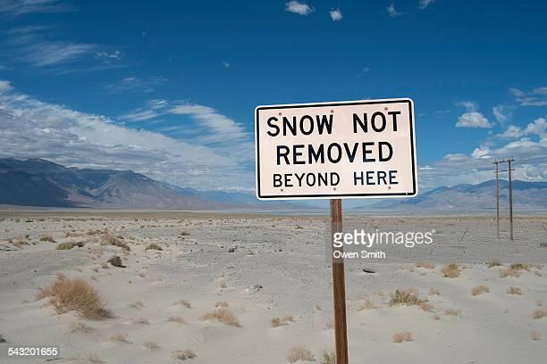 Snow warning sign in desert, Death Valley, California, USA