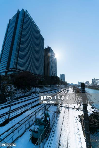 Snow wraps up the Japan Railway Company Chuo Line and Sobu Line railway track along the Kanda River around Iidabashi Station, which are illuminated by sunlight over the sky at Chiyoda-ku Tokyo Japan – January. 23 2018. The day after the winter blizzard.