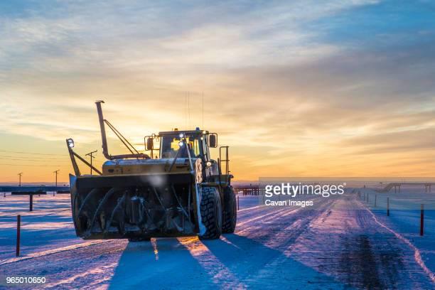 snowblower at field against dramatic sky during sunset - schneefahrzeug stock-fotos und bilder