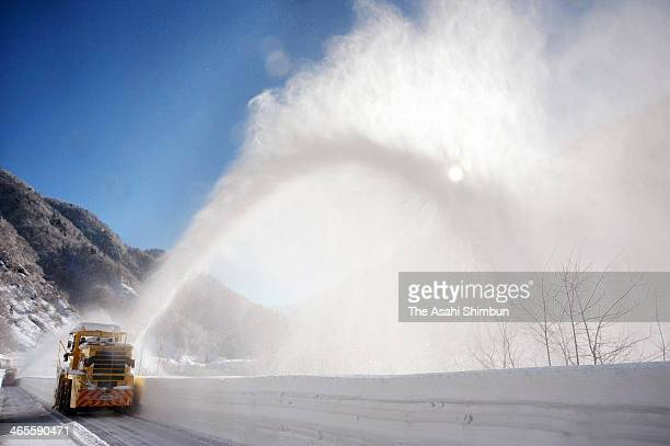 A snowblower discharge snow outside the road during the snow removal operation at the TateyamaKurobe Alpine Route on January 27 2014 in Tateyama...