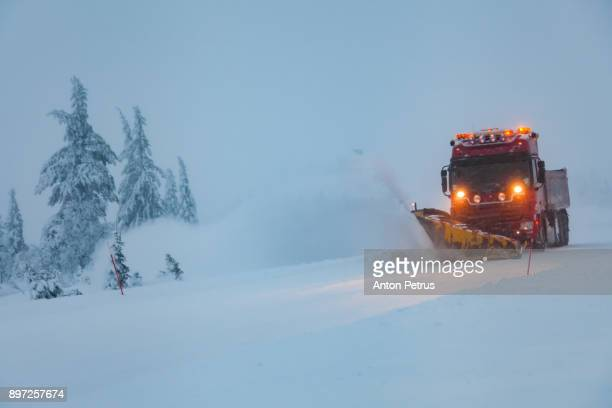 snowblower grader clears snow covered country road - snow storm stock photos and pictures