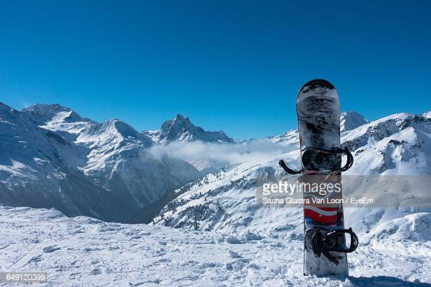 b2ebe5d4ba06 Snowboard By Snowcapped Mountains Against Clear Blue Sky