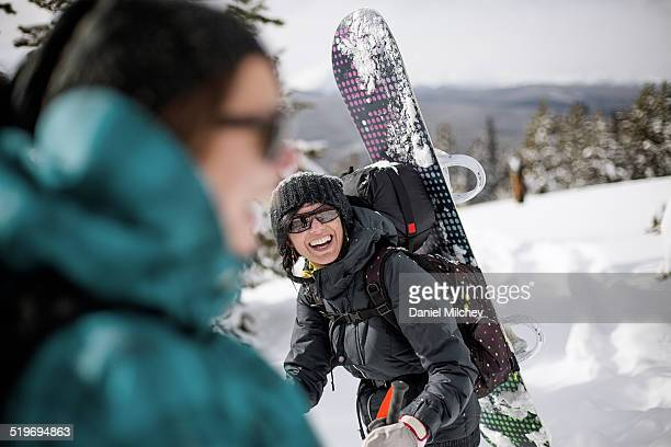 snowboard girls laughing, while hiking on mountain - outdoor pursuit stock pictures, royalty-free photos & images