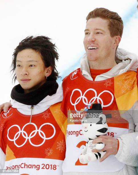 Snowboard halfpipe gold medalist Shaun White of the United States and silver medalist Ayumu Hirano of Japan stand shoulder to shoulder after the...