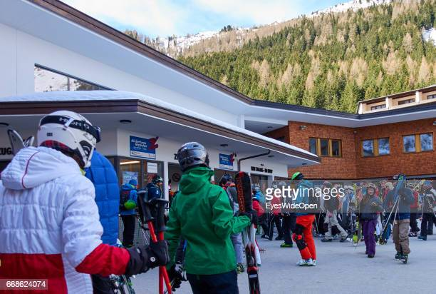 Snowboarder and alpine skiers on the way to the cableway on the glacier of Hintertux on March 12 2017 in Hintertux Austria