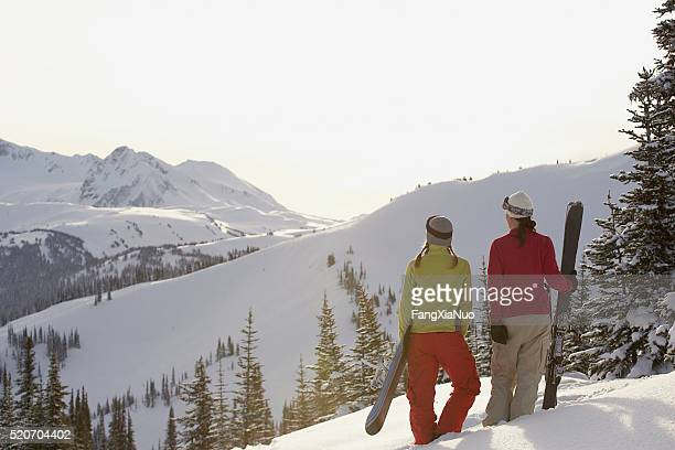 Snowboarder and skier in the mountains