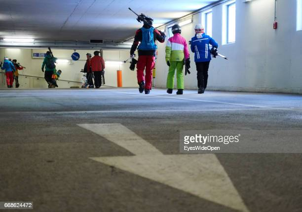 Snowboarder and skiers in the car parking area on the way to the cableway on the glacier of Hintertux on March 12 2017 in Hintertux Austria