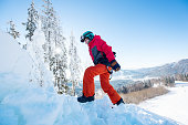 Snowboarder carrying his board walking in the winter mountains on sunny day copyspace active sports lifestyle recreation people
