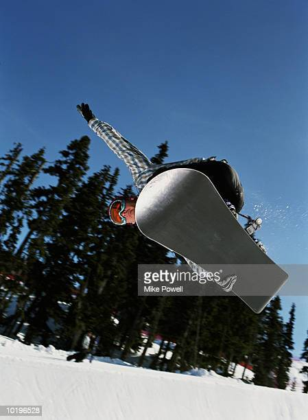 Snowboarder catching air off lip of half pipe, low angle view
