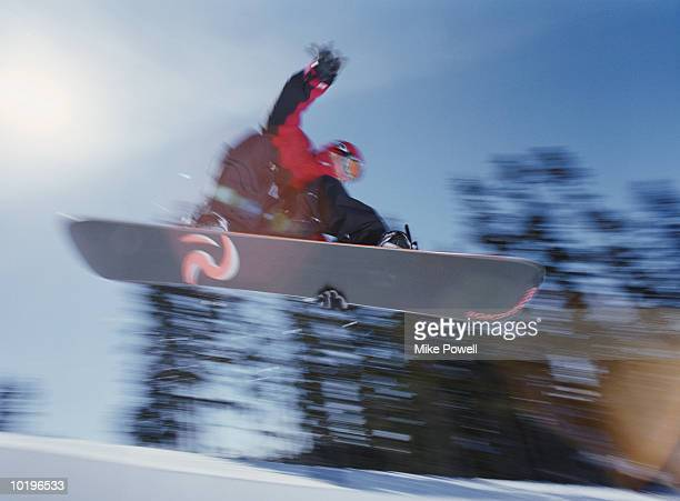 Snowboarder catching air off of half pipe, low angle view (Blurred Mot
