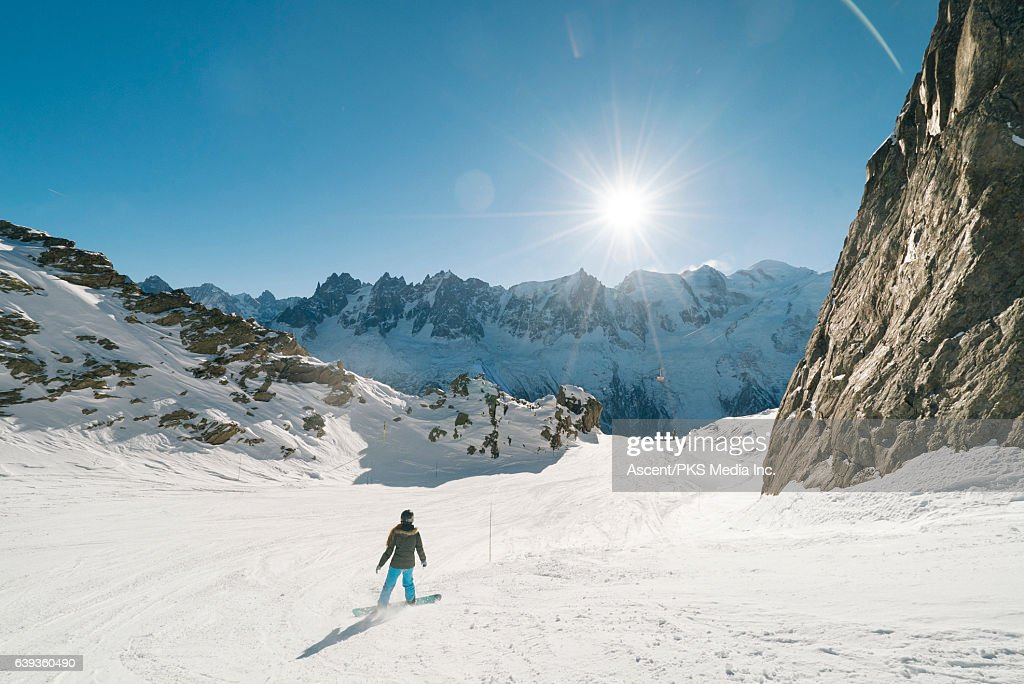 Snowboarder descends empty mountain slope : Stock Photo