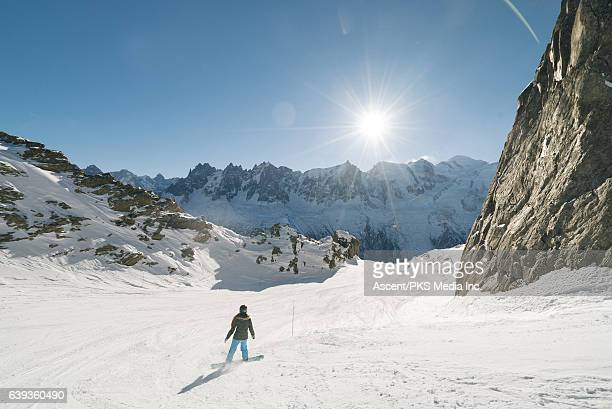 Snowboarder descends empty mountain slope