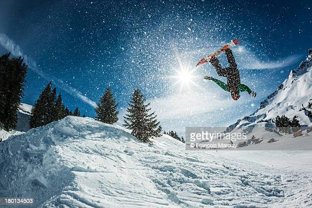 snowboarder doing a backflip with snow exploding - boarding stock pictures, royalty-free photos & images
