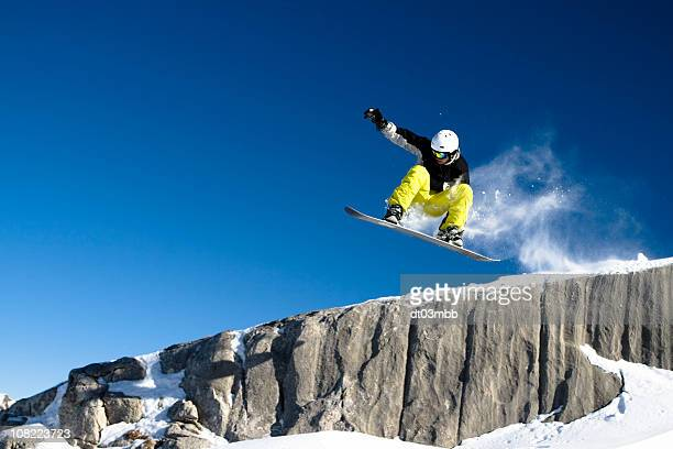 Snowboarder Dropping Off Short Cliff Against Blue Sky