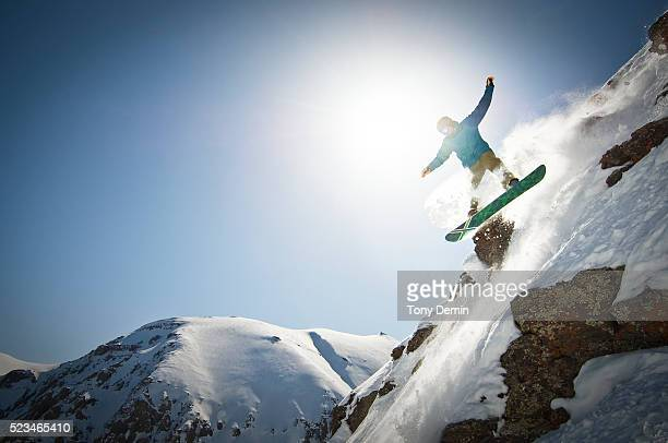 Snowboarder going over cliff