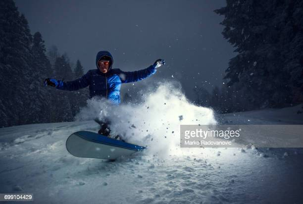 Snowboarder in action lit by strobe