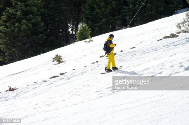Snowboarder in drag lift going uphill