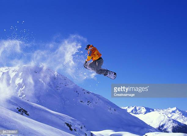 Snowboarder in mid-jump with a cloud of snow trailing behind