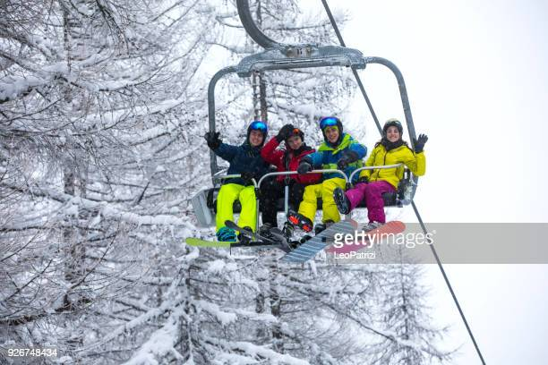 snowboarder in the alps - group of friends having fun in a winter vacation - ski lift stock pictures, royalty-free photos & images