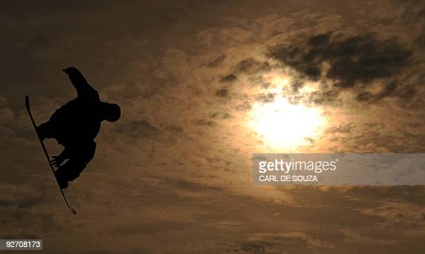 A snowboarder is silhouetted as he takes part in a qualifying session at the Battersea power station in London on October 30 2009 The session took...