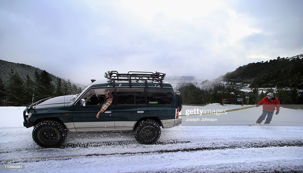 A snowboarder is towed by a 4WD along the Summit Road on the Port Hills on June 21, 2013 in Christchurch, New Zealand. Now, sleet, rain and heavy winds have hit the region causing power outages, some flooding and bringing trees down.
