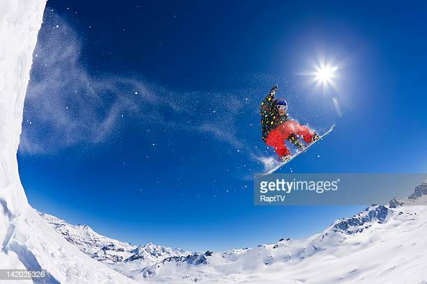Snowboarder jumping across snowy mountain