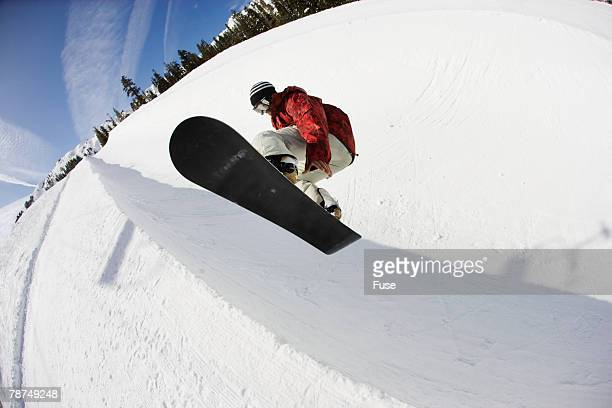 Snowboarder Jumping in a Halfpipe