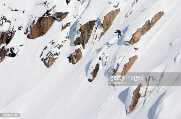 a snowboarder jumping off a cliff on a sunny day at cerro catedral in argentina - リオネグロ州 ストックフォトと画像