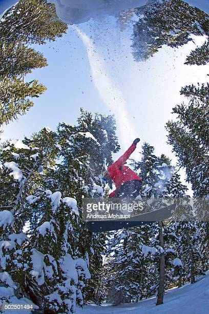 A Snowboarder jumping off a cliff