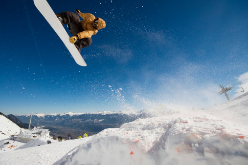 Snowboarder jumping off mountain - gettyimageskorea